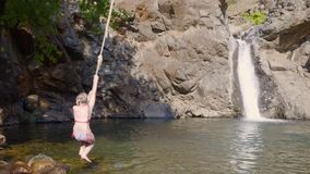 Girl teenager jumping in mountain river from bungee on flowing waterfall landscape. Teenager girl diving to waterfall. Lake from bungee rope in tropical forest stock footage