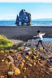Girl teenager is jumping over water stream in the border of Hindisvik bay in Northwest Iceland, the Hvitserkur basalt stack is at stock image