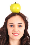 Girl-teenager keeps on head a apple Royalty Free Stock Photos