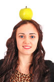 Girl-teenager keeps on head a apple Royalty Free Stock Image