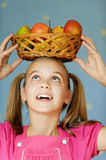 Girl-teenager keeps on his head. Beautiful blue-eyed laughing girl-teenager in pink dress keeps on his head basket of apples, on blue background Royalty Free Stock Images