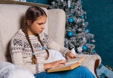 Teenager in a knitted sweater sits in an armchair by the Christmas tree and reads a book. Girl teenager in a knitted sweater sits in an armchair by the Christmas Royalty Free Stock Image