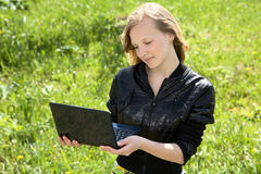 Girl-teenager with the laptop. Against a green grass in the sunny day Royalty Free Stock Image