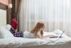 Girl teenager with laptop in bed Stock Photography