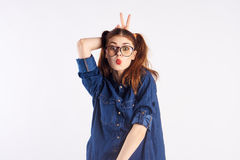 Girl teenager on a light background with glasses, emotions, fooling around Stock Photo