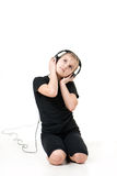 Girl teenager listening to music with big headphones and looking up pensively. Little girl listening to music with big headphones happy delight Stock Photo