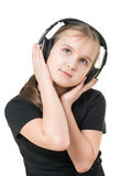 Girl teenager listening to music with big headphones and looking up pensively Stock Photos