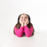 Girl teenager listening to music with big headphones and looking up pensively. Little girl listening to music with big headphones happy delight Royalty Free Stock Photography