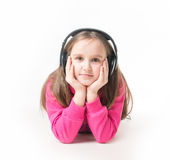 Girl teenager listening to music with big headphones and looking up pensively. Little girl listening to music with big headphones happy delight Stock Photos