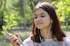 Girl teenager listening to music from a mobile phone. Portrait of a girl in headphones close-up. A young girl listens to music fro. M the device. Communication stock photography