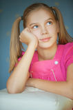 Girl-teenager looking up. Beautiful blue-eyed girl-teenager looking up and dreaming, on blue background Royalty Free Stock Images