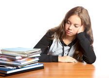 The girl-teenager looks at  pile of books Royalty Free Stock Photography