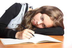 The girl-teenager looks in  writing-book Stock Image