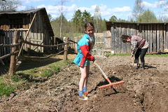 Girl teenager loose soil using a hand garden tools, Russia. Stock Images
