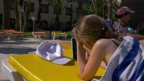 Girl teenager lying on chaise longue near swimming pool and using mobile phone. Daughter and mother on sun beds sunbathing and using smartphones stock footage