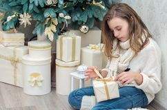 Girl teenager opens presents crouched. Beside decorated Christmas tree Stock Photo