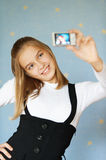 Girl-teenager photographed itself. Beautiful blue-eyed girl-teenager photographed with camera itself, on blue background Royalty Free Stock Photo