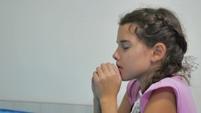 Girl teenager prays before bedtime. kneeling by the bed of a girl and praying the religion of faith indoor stock video