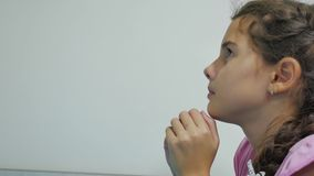 Girl teenager prays before bedtime. kneeling by the bed of a indoor girl and praying the religion of faith stock video