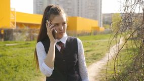 Schoolgirl comes home from school. Girl teenager talks to his mom on the phone on the way home.