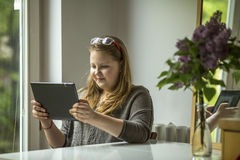 Girl teenager sitting at a table with tablet in hands. Happy. Stock Photo