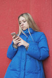 Girl teenager standing near a red wall uses a smartphone Stock Images