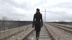 Girl teenager stands on the tram bridge, turns and walks away. Overcast stock footage