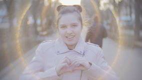 Portrait of an attractive young teen girl looking at the camera and smiling. Close shot. Girl teenager on the street laughing and looking at the camera Close stock footage