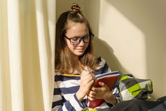 Girl teenager is studying at home. Sitting in bed writing in school notebook. Girl teenager is studying at home. Sitting in bed writing in school notebook Stock Photos