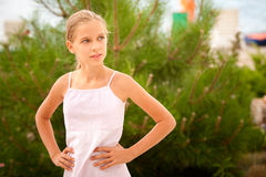 Girl-teenager on summer vacations. Young beautiful schoolgirl against green cedar during summer vacations Stock Photo
