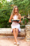 Girl-teenager on summer vacations. Young schoolgirl reads textbook on summer vacations for preparation for new academic year Royalty Free Stock Photos
