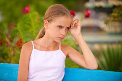 Girl-teenager on summer vacations. Girl sits on blue bench and thinks of life, against blossoming summer lawns Stock Photos