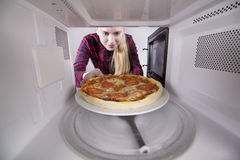 Girl teenager take out pizza from the microwave Royalty Free Stock Image
