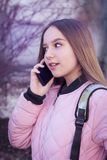 Girl teenager talking on the phone outdoors. A teenage girl talking on the phone outdoors, smiling and looking away Stock Images