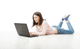 Girl teenager using wireless laptop. Woman Typing in computer lying on white floor.