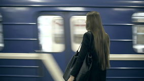 Girl teenager waiting for the subway train waits and comes aboard stock footage