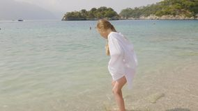 Girl teenager walking to sea on pebble beach. Tourist girl enjoying sea water at sunny day. Young girl spending summer stock video