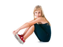 The girl the teenager on a white background. The girl the teenager in black clothes and red gym shoes. In studio on a white background Stock Photos