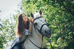 Girl teenager and white horse in a park in a summer. Day Royalty Free Stock Image