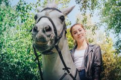 Girl teenager and white horse in a park in a summer royalty free stock photos