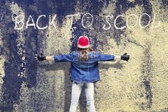 Girl teenager with widely apart hands. Denim clothing. Baseball cap. Against the background of the old concrete wall. Inscription royalty free stock photo