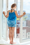 Girl teenager is on window with opened door, looking down from height Stock Photo