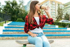 Girl teenager 13-16 years old schoolgirl, sits on a skateboard steps. In the summer in city after classes, drink a drink. Girl teenager 12-15 years old stock photos