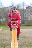 A girl teeters on a seesaw Royalty Free Stock Photo