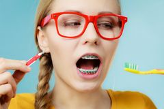 Girl with teeth braces using interdental and traditional brush. Dentist and orthodontist concept. Young woman with blue braces cleaning and brushing teeth using Stock Image