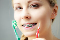 Girl with teeth braces using interdental and traditional brush. Dentist and orthodontist concept. Young woman with blue braces cleaning and brushing teeth using Stock Images