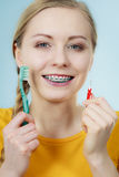 Girl with teeth braces using interdental and traditional brush. Dentist and orthodontist concept. Young woman with blue braces cleaning and brushing teeth using Stock Photo