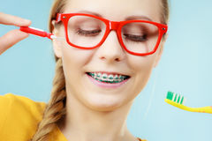 Girl with teeth braces using interdental and traditional brush. Dentist and orthodontist concept. Young woman with blue braces cleaning and brushing teeth using Stock Photos