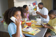 Girl (6-8) on telephone by family at breakfast table, smiling, portrait Royalty Free Stock Photos