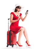 Girl with telephone sitting on suitcase Stock Image